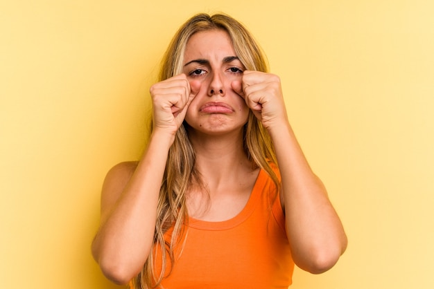 Jonge blanke blonde vrouw geïsoleerd op gele achtergrond jammerend en huilend troosteloos.