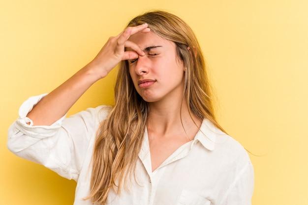 Jonge blanke blonde vrouw geïsoleerd op gele achtergrond met hoofdpijn, aanraken van de voorkant van het gezicht.