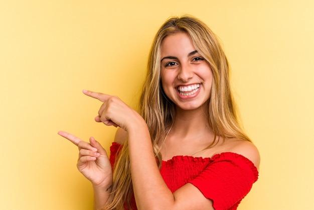 Jonge blanke blonde vrouw geïsoleerd op gele achtergrond opgewonden wijzend met wijsvingers weg.