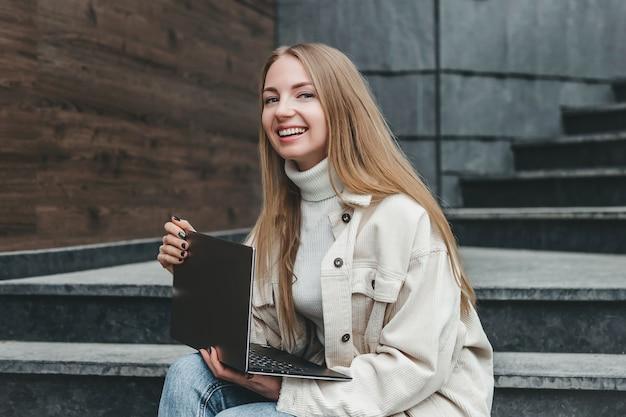 Jonge blanke blonde vrouw it-specialist zittend op trappen in de buurt van kantoorgebouw met laptop lachend