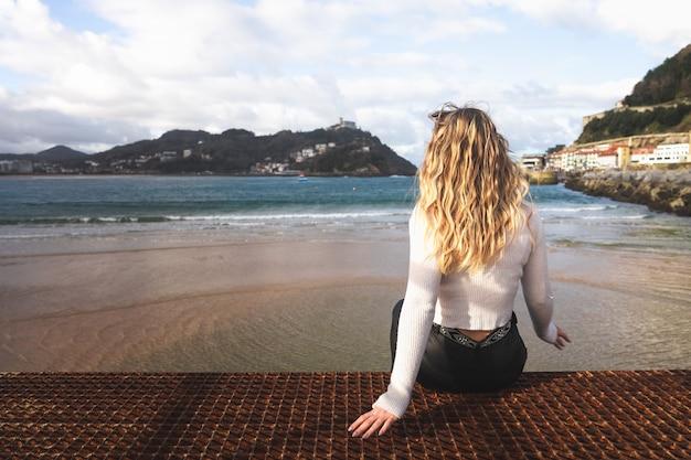 Jonge blanke blonde vrouw op de pier van donostia-san sebastian baskenland.