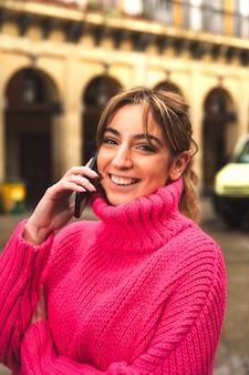 Jonge blanke blonde vrouw praten via de telefoon op straat
