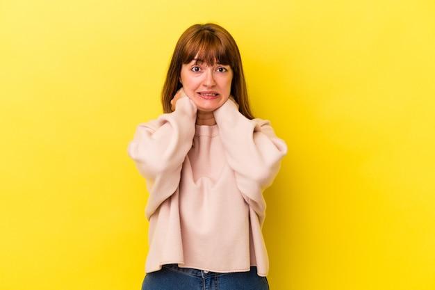 Jonge blanke bochtige vrouw geïsoleerd op gele achtergrond achterhoofd aanraken, denken en een keuze maken.