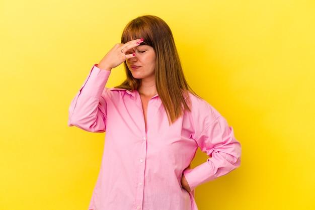 Jonge blanke bochtige vrouw geïsoleerd op gele achtergrond met hoofdpijn, aanraken van de voorkant van het gezicht.