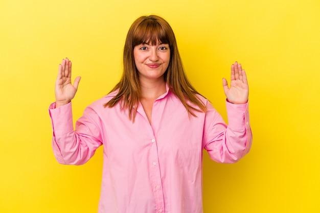 Jonge blanke bochtige vrouw geïsoleerd op gele achtergrond met iets kleins met wijsvingers, glimlachend en zelfverzekerd.