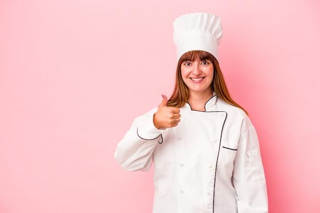 Jonge blanke chef-kokvrouw geïsoleerd op roze achtergrond glimlachend en duim omhoog