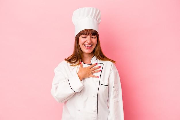 Jonge blanke chef-kokvrouw geïsoleerd op roze achtergrond lacht hardop terwijl ze de hand op de borst houdt.