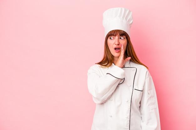 Jonge blanke chef-kokvrouw geïsoleerd op roze achtergrond zegt een geheim heet remnieuws en kijkt opzij