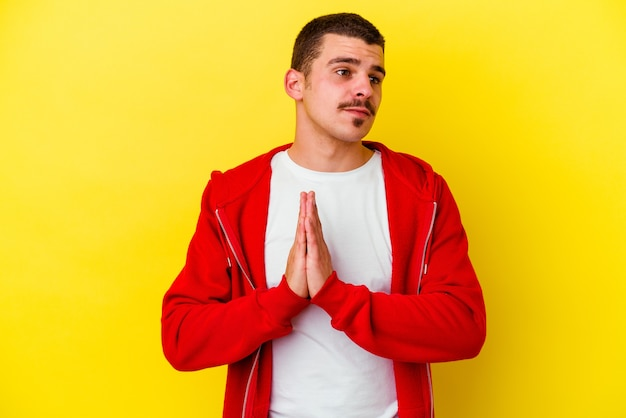 Jonge blanke coole man geïsoleerd op gele muur bidden, toewijding tonen, religieuze persoon op zoek naar goddelijke inspiratie
