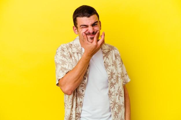 Jonge blanke coole man geïsoleerd op gele muur twijfelen tussen twee opties