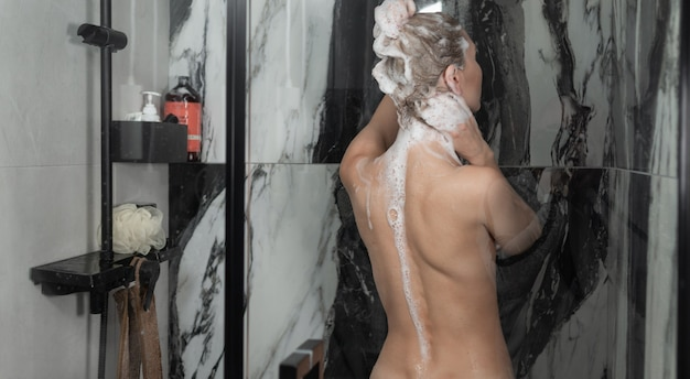 Jonge blanke dame neemt een douche. shampoo je haar. lichaams- en haarverzorging. achteraanzicht,