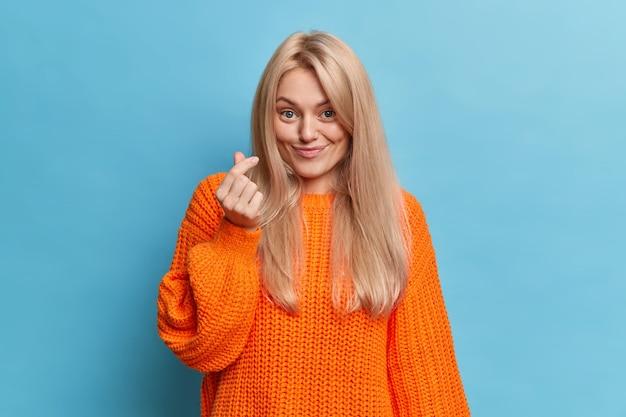 Jonge blanke dame toont mini hart handgebaar heeft een aangename glimlach gekleed in een casual oranje trui