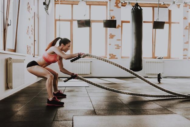 Jonge blanke dame traint met touwen.