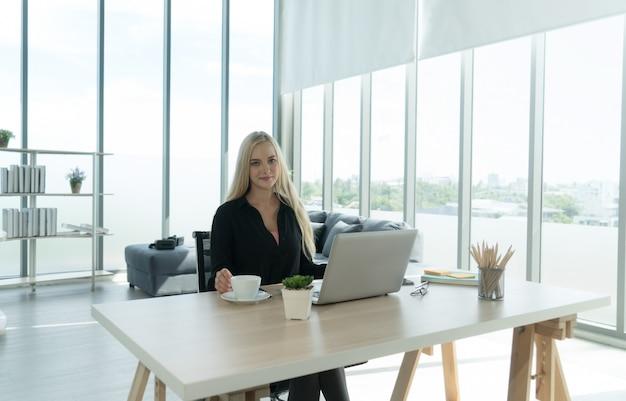 Jonge blanke etnische vrouw student freelancer glimlachend werken studeren op laptop notebook computer doet onderzoek thuis bureau met koffiekopje.