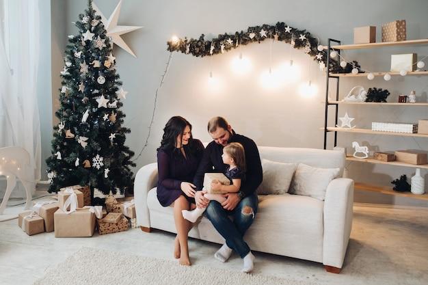 Jonge blanke familie van drie zit samen op de bank naast de kerstboom