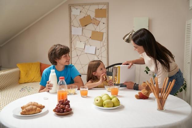 Jonge blanke familiemoeder en haar twee schattige kleine kinderen glimlachen en communiceren zittend