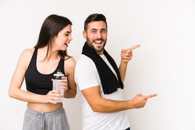 Jonge blanke fitness paar geïsoleerd opgewonden wijzend met wijsvingers weg.