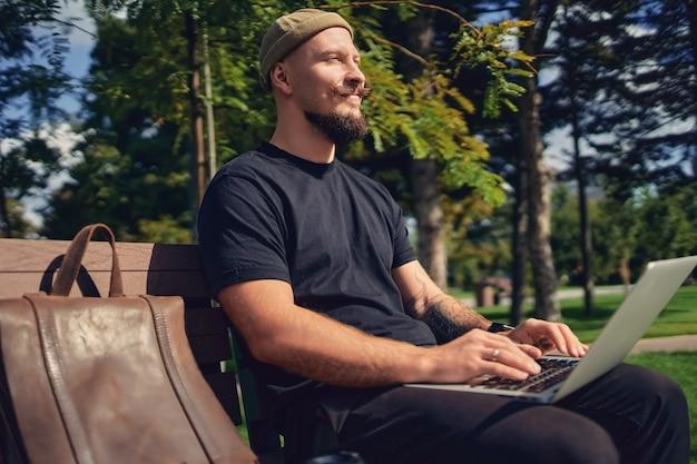 Jonge blanke freelancer zit op de bank in het park met laptop en geniet van ontspannen vrije tijd
