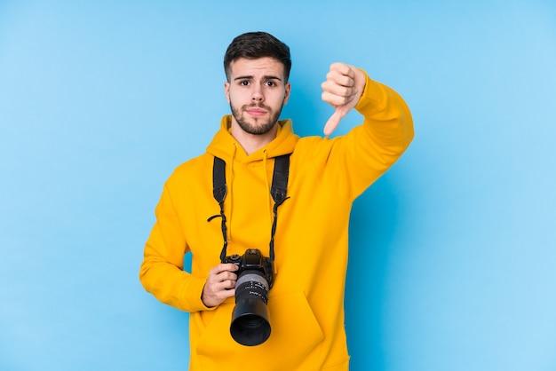 Jonge blanke geïsoleerde fotograaf man met een afkeer gebaar, duimen naar beneden. meningsverschil concept.