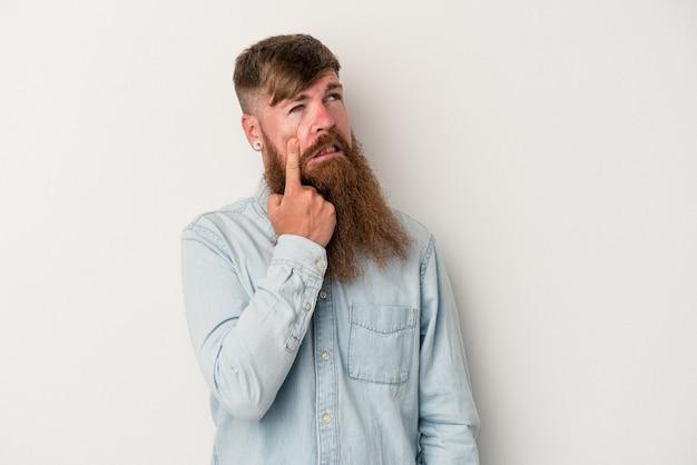 Jonge blanke gember man met lange baard geïsoleerd op een witte achtergrond huilen, ongelukkig met iets, pijn en verwarring concept.