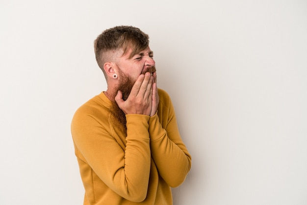 Jonge blanke gember man met lange baard geïsoleerd op een witte achtergrond lachen om iets, mond bedekken met handen.