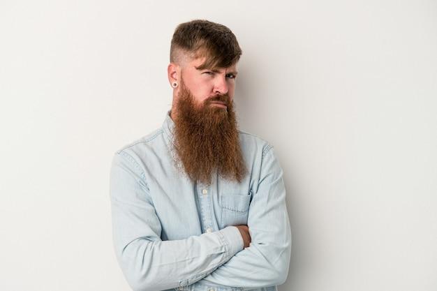 Jonge blanke gember man met lange baard geïsoleerd op een witte achtergrond ongelukkig in de camera kijken met sarcastische uitdrukking.