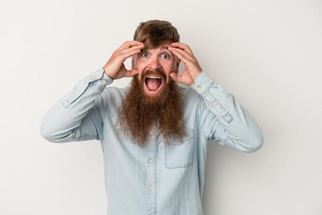 Jonge blanke gember man met lange baard geïsoleerd op een witte achtergrond ontvangen een aangename verrassing, opgewonden en handen opsteken.