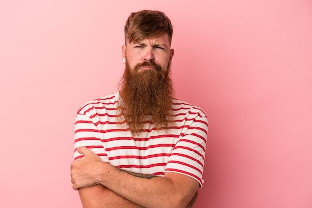 Jonge blanke gember man met lange baard geïsoleerd op roze achtergrond fronsend gezicht in ongenoegen, houdt armen gevouwen.