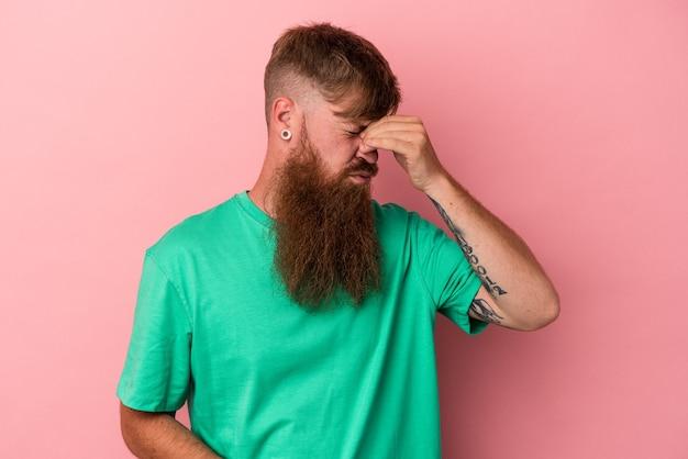 Jonge blanke gember man met lange baard geïsoleerd op roze achtergrond met hoofdpijn, voorkant van het gezicht aan te raken.