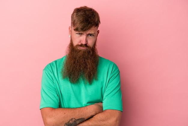 Jonge blanke gember man met lange baard geïsoleerd op roze achtergrond ongelukkig in de camera kijken met sarcastische uitdrukking.