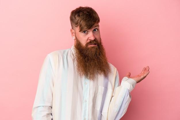 Jonge blanke gember man met lange baard geïsoleerd op roze achtergrond twijfelen en schouders ophalen in ondervraging gebaar.