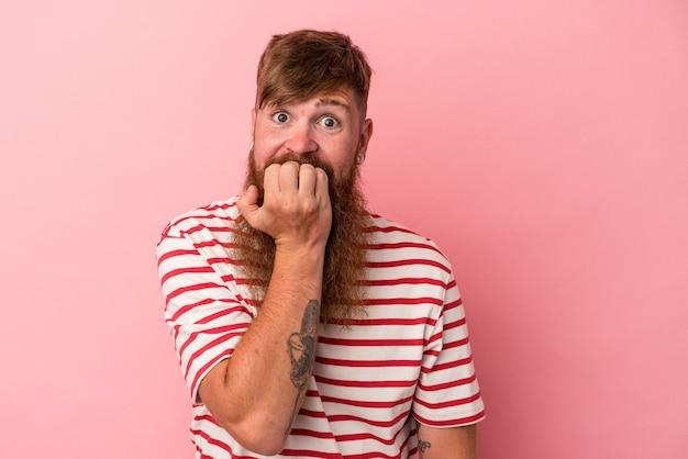 Jonge blanke gemberman met lange baard geïsoleerd op roze achtergrond bijtende vingernagels, nerveus en erg angstig.
