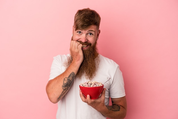 Jonge blanke gemberman met lange baard met een kom cornflakes geïsoleerd op roze achtergrond bijtende vingernagels, nerveus en erg angstig.