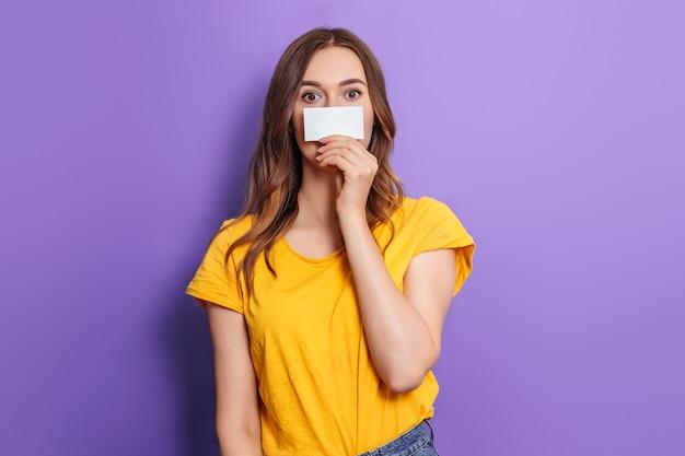 Jonge blanke geschokte vrouw die een visitekaartje in haar handen houdt en haar gezicht bedekt dat op een lila achtergrond in de studio wordt geïsoleerd. krediet online. mockup