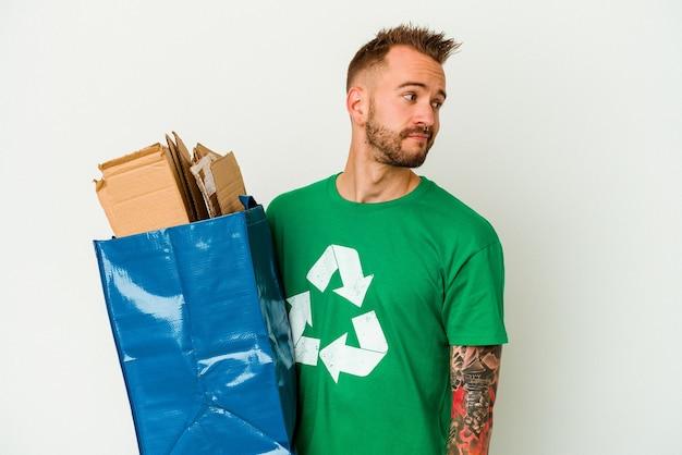 Jonge blanke getatoeëerde man gerecycled karton geïsoleerd op een witte achtergrond kijkt opzij lachend, vrolijk en aangenaam.