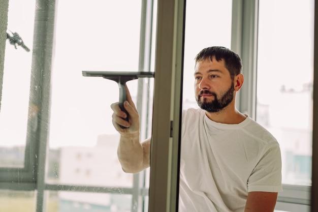 Jonge blanke glimlachende man die het raam wast met een rakelreinigingsconcept