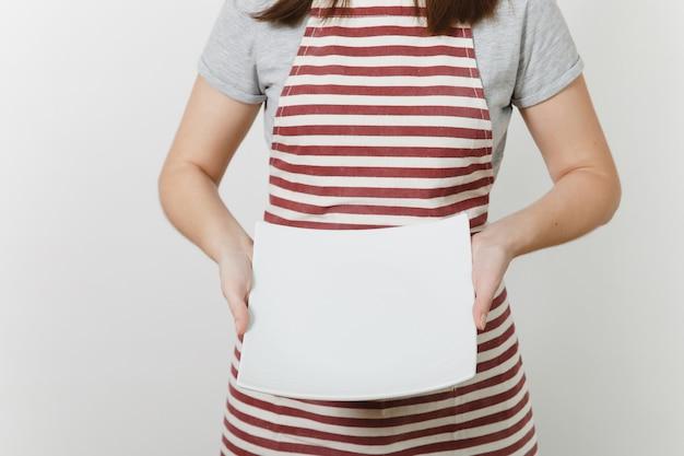 Jonge blanke huisvrouw in gestreepte schort, grijs t-shirt geïsoleerd. huishoudster vrouw met in handen witte lege vierkante plaat