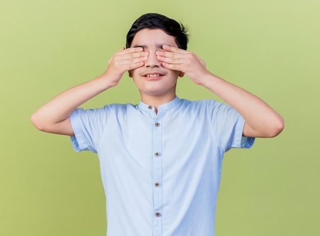 Jonge blanke jongen die ogen behandelt met handen die op olijfgroene muur worden geïsoleerd