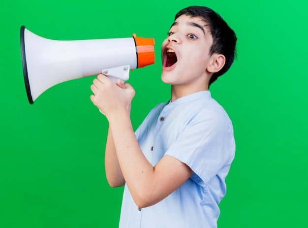 Jonge blanke jongen die zich in profielweergave bevindt die door spreker spreekt die op groene achtergrond met exemplaarruimte wordt geïsoleerd