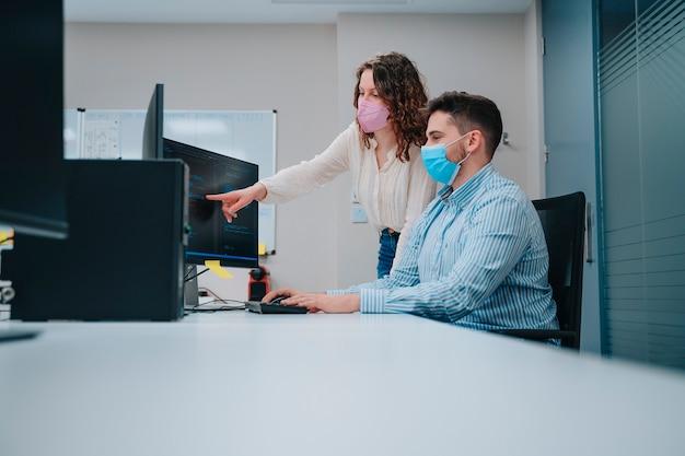 Jonge blanke jongen en vrouw die gezichtsmaskers dragen collega's in een computer