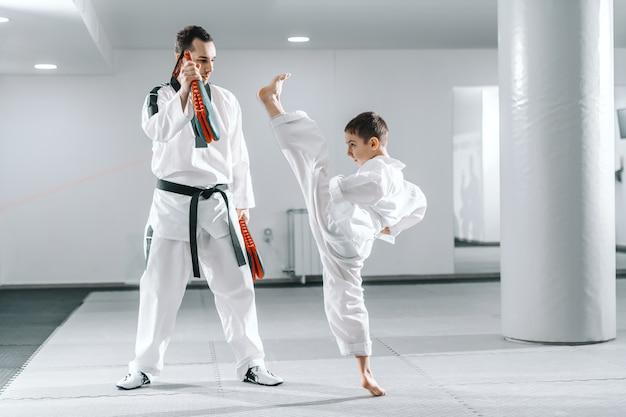 Jonge blanke jongen in dobok blootsvoets schoppen terwijl trainer met kick doel. taekwondo trainingsconcept.