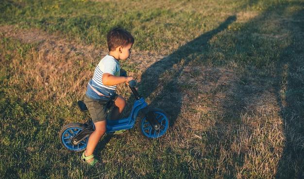Jonge blanke jongen met een fiets op een groen veld heeft vreugde in een zonnige zomeravond