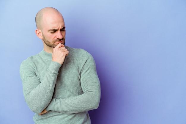 Jonge blanke kale man geïsoleerd op paarse muur zijwaarts op zoek met twijfelachtige en sceptische uitdrukking