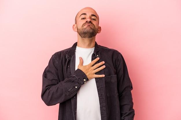 Jonge blanke kale man geïsoleerd op roze achtergrond die een eed aflegt, hand op de borst.