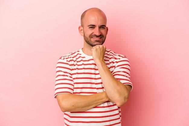 Jonge blanke kale man geïsoleerd op roze achtergrond glimlachend gelukkig en zelfverzekerd, kin met hand aanraken.