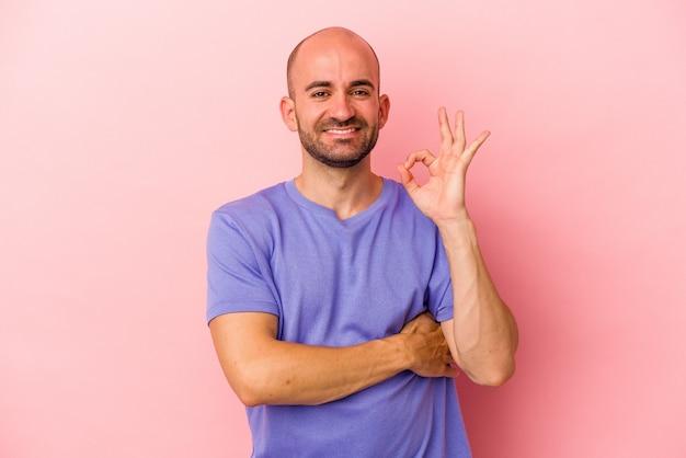 Jonge blanke kale man geïsoleerd op roze achtergrond knipoogt en houdt een goed gebaar met de hand.