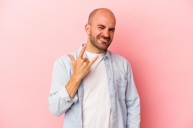 Jonge blanke kale man geïsoleerd op roze achtergrond met rotsgebaar met vingers