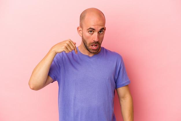 Jonge blanke kale man geïsoleerd op roze achtergrond persoon die met de hand wijst naar een shirt kopieerruimte, trots en zelfverzekerd