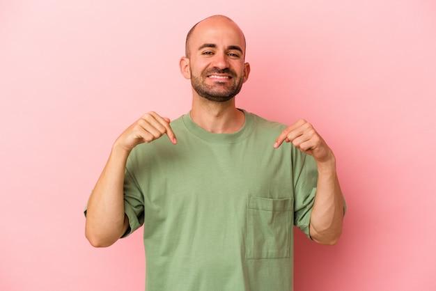 Jonge blanke kale man geïsoleerd op roze achtergrond wijst naar beneden met vingers, positief gevoel.