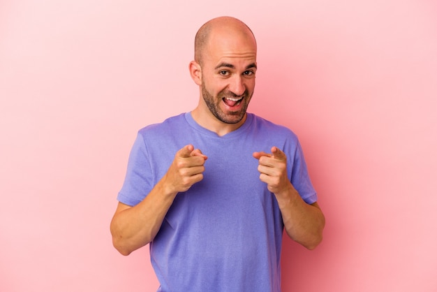 Jonge blanke kale man geïsoleerd op roze achtergrond wijzend naar voren met vingers.